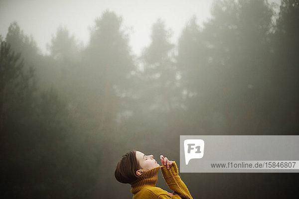 Nachdenkliche Frau steht bei nebligem Wetter am Wald