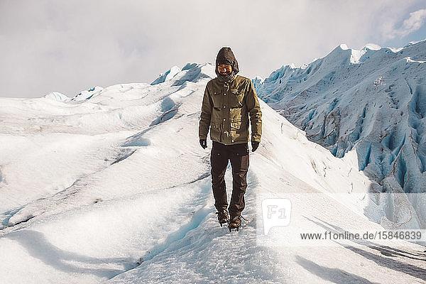 Männlicher Entdecker lächelt und geht auf dem Gletscher
