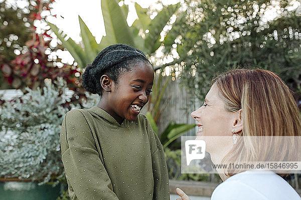 Lachende weiße Mutter und schwarze Tochter vor üppigem Grün