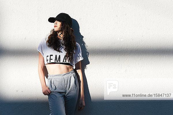 Attraktive trendige Frau  die an einer weißen Wand mit horizontalen Schatten lehnt