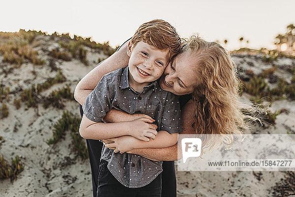 Frontansicht einer Mutter  die einen rothaarigen Sohn im Kindergartenalter bei Sonnenuntergang umarmt