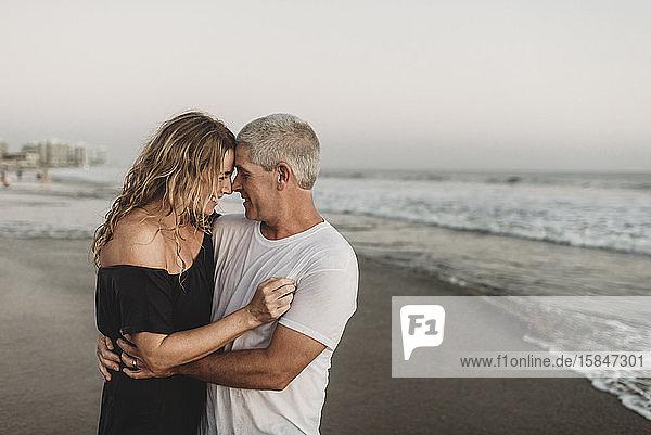 Seitenansicht eines Ehepaares  das sich im Meer umarmt