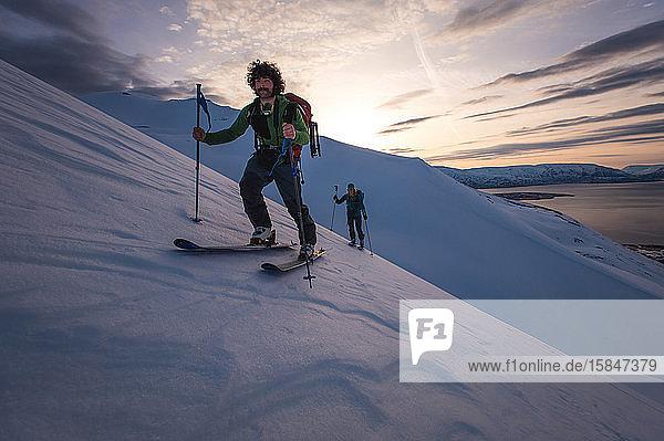 Mann und Frau beim Skilanglauf in Island mit Wasser im Rücken