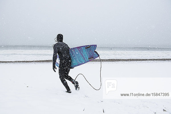 Mann geht im Winterschnee surfen