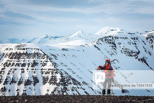 Frau steht mit Skiern mit Bergen im Rücken in Island