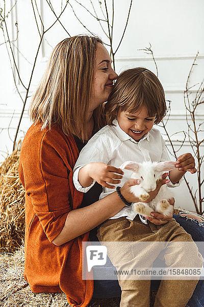 Osterkinder spielen mit Kaninchen und Enten