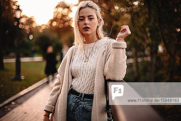 Porträt einer selbstbewussten jungen Frau  die im Herbst im Park steht