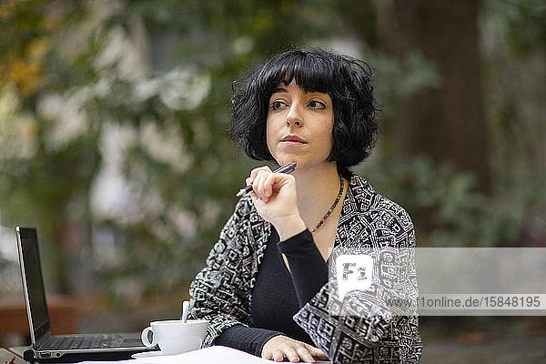 junge Frau mit Laptop im Freien beim Kaffeetrinken