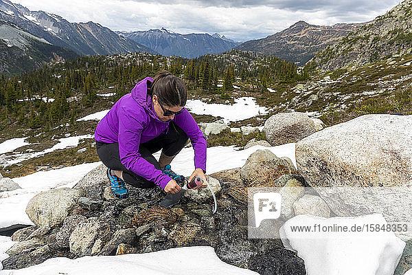 Eine Frau kauert sich hin und benutzt einen Wasserfilter  um Trinkwasser aus einem kleinen alpinen Bach in den Bergen von Britisch-Kolumbien zu gewinnen.