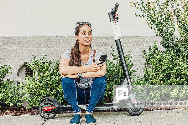 Woman Sits on Scooter
