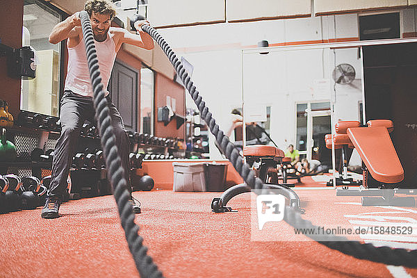 Active man exercising with battling rope at fitness club