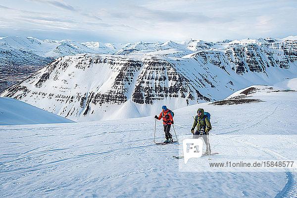 Mann und Frau beim Skifahren in Island mit Bergen im Hintergrund