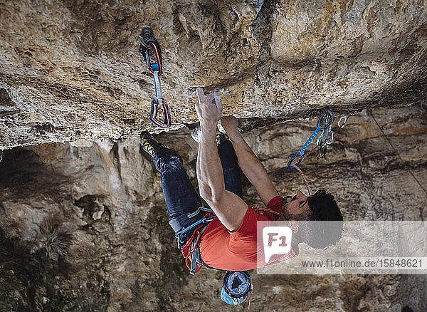 Luftaufnahme eines Kletterers auf einer harten Sportkletterroute in einer Höhle.