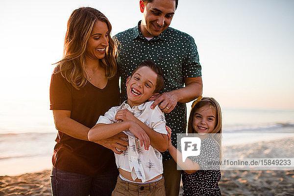 Vierköpfige Familie spielt & lächelt am Strand bei Sonnenuntergang