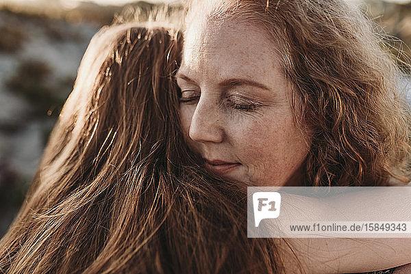 Detailaufnahme des Gesichts einer Mutter  die ihre Tochter am Strand umarmt