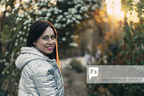 Junge braunhaarige Frau in einem Park bei Sonnenuntergang