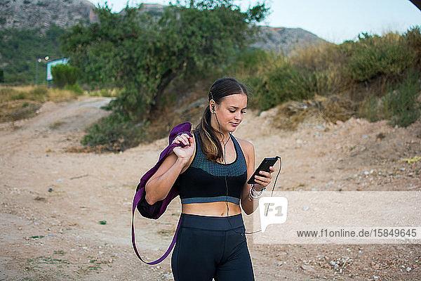 Junge Frau beobachtet ihr Smartphone nach dem Sport