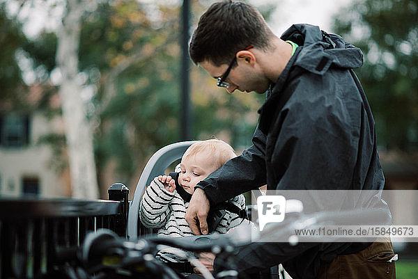 Ein junger  tausendjähriger Vater  der seinen Sohn in den Fahrradsitz schnallt.
