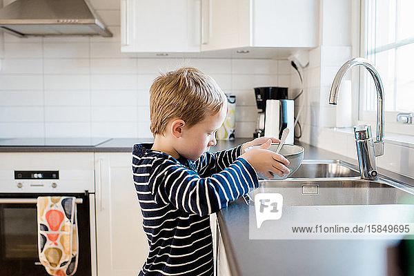 Junge hilft nach dem Frühstück vor der Schule beim Abwasch