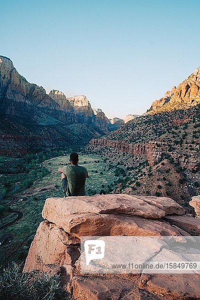 Schwarzer Mann auf einem Felsen  der bei Sonnenuntergang den Berg betrachtet