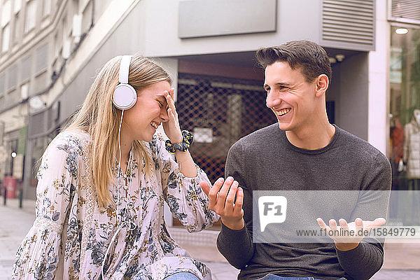 attraktives junges junges Paar unterhält sich lachend und unterhaltsam angeregt auf einer Bank auf der Straße sitzend