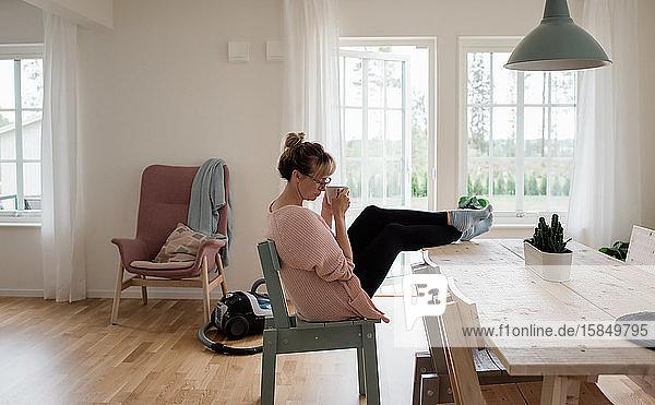 Frau  die zu Hause sitzt und Hausarbeit vermeidet und eine Tasse Tee trinkt