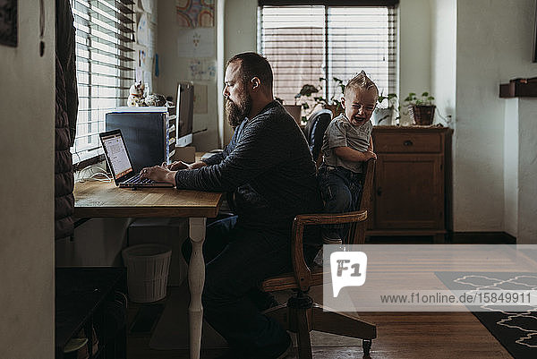Dad working from home with one year old boy crying while he works