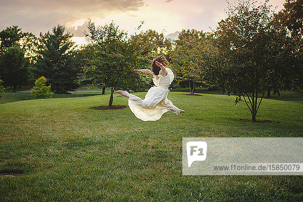 Eine Tänzerin springt in einem langen weißen Kleid in einem von Bäumen gesäumten Park bei Sonnenuntergang