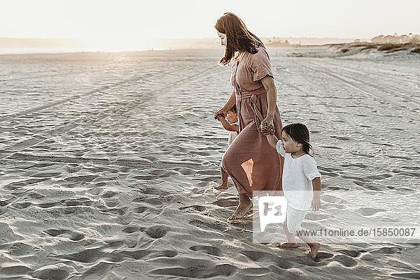 Seitenansicht einer Mutter  die mit ihren kleinen Zwillingen bei Sonnenuntergang zum Meer läuft