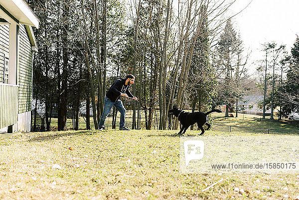 Ein junger Mann spielt mit seinem Hund.