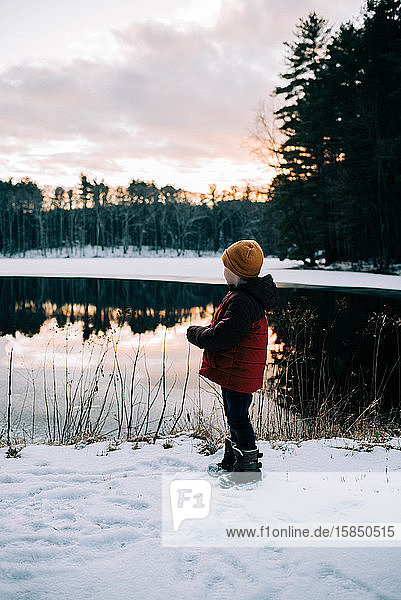 Little boy by a half frozen lake during sunset.