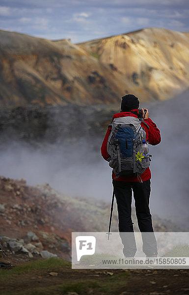 Frau hält an  um die Aussicht auf den Laugavegur-Wanderweg zu bewundern