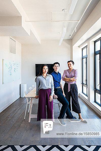 Porträt von selbstbewussten männlichen und weiblichen Mitarbeitern im Sitzungssaal im Büro
