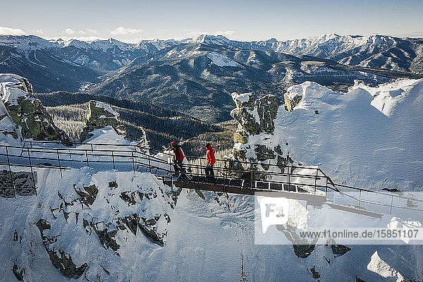 Skiers hiking on top of cliffs