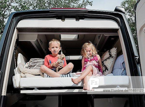 Bruder und Schwester saßen im Sommer auf einem Bett in einem Wohnmobil im Urlaub