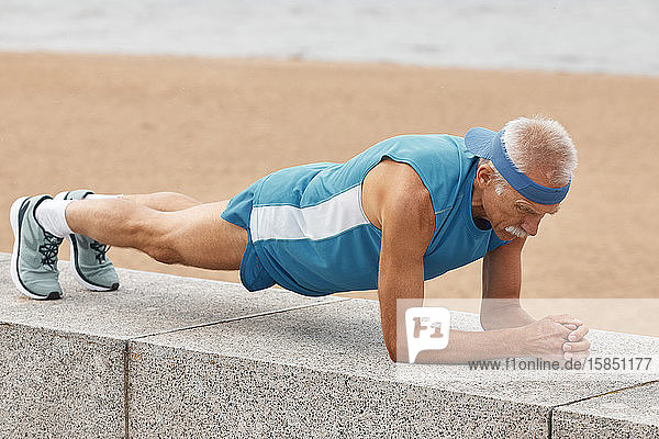 Mann übt Delphin-Planken-Pose