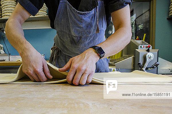 Nahaufnahme eines professionellen Bäckers  der Teig auf bemehlter Oberfläche bearbeitet
