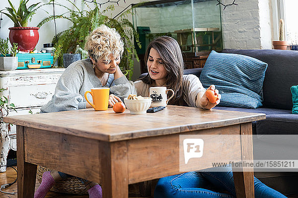 Freundinnen  die während des Kaffeetrinkens am Wohnzimmertisch auf ihr Handy schauen