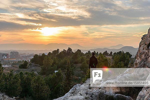 Ein Mann betrachtet die Stadt  während er auf dem Berg ist. Er hat einen Rucksack