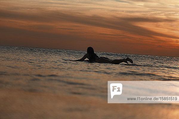 Weibliche Surferin bei Sonnenuntergang im Ozean