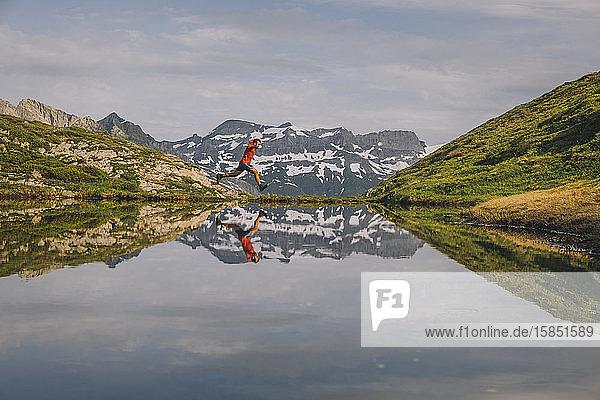 Ein Wanderer springt im Tal von Chamonix in einem Bergsee  der sich in ihm spiegelt.