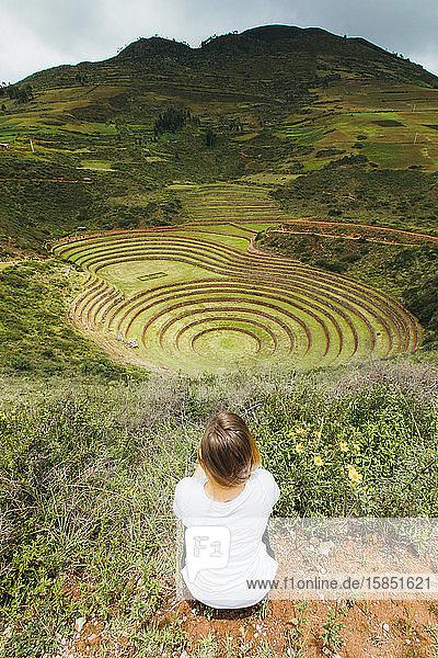 Eine junge Frau sitzt in der Nähe des berühmten peruanischen Fleckens Moray in Peru