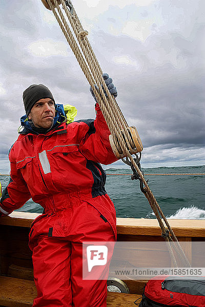 Ein Mann in einem alten Segelboot mit einem Sicherheitsanzug in arktischen Gewässern (Island)