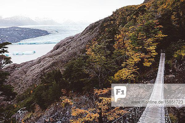 Suspension bridge between rocks next to lake