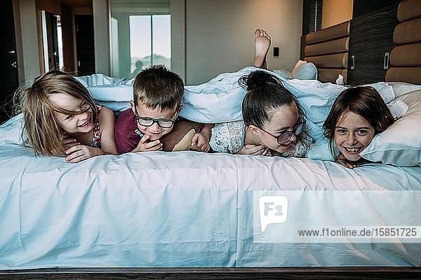 Kinder  die im Urlaub im Hotelzimmer auf dem Bett liegen