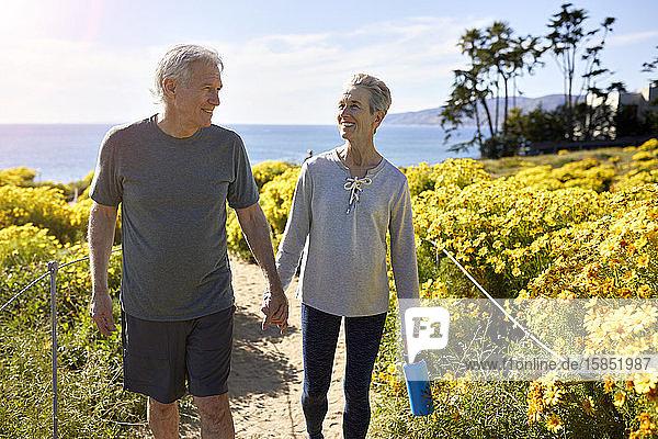 Lächelndes älteres Ehepaar hält sich an den Händen,  während es am sonnigen Tag auf einem Pfad inmitten von Pflanzen auf einer Klippe am Meer gegen den Himmel geht