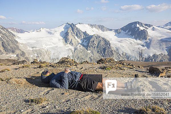 Wanderer auf Berggipfel liegend  erschöpft nach einem langen Tag