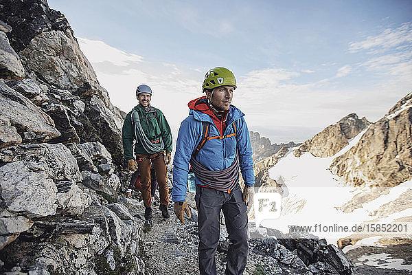 Zwei Felskletterer mit Helm und Seilen gehen an einer Klippe in Tetons entlang
