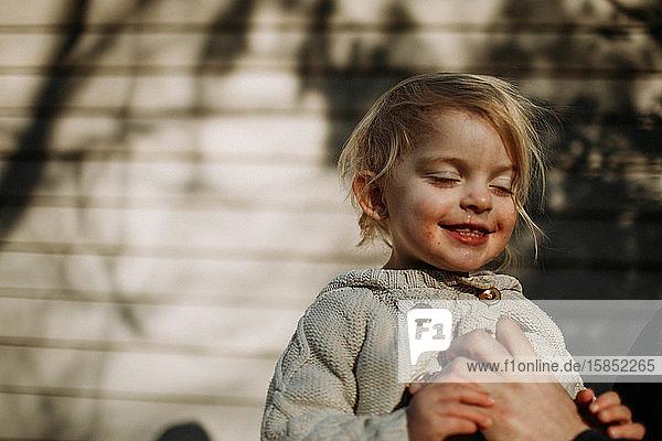 Kleinkind lächelt mit geschlossenem Mund im Sonnenlicht