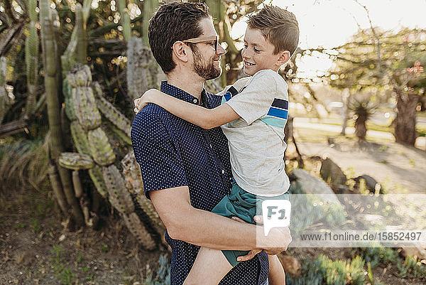 Porträt eines Vaters  der einen älteren Sohn hält und einander anlächelt